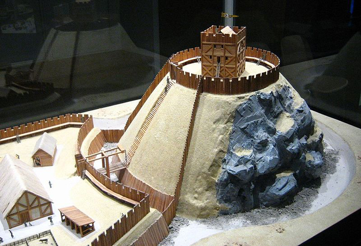 Model of a typical Motte and Bailey Castle, showing the artificial mound surmounted by a wooden keep, (the Motte), and the fenced enclosure surrounded by a ditch (the Bailey).